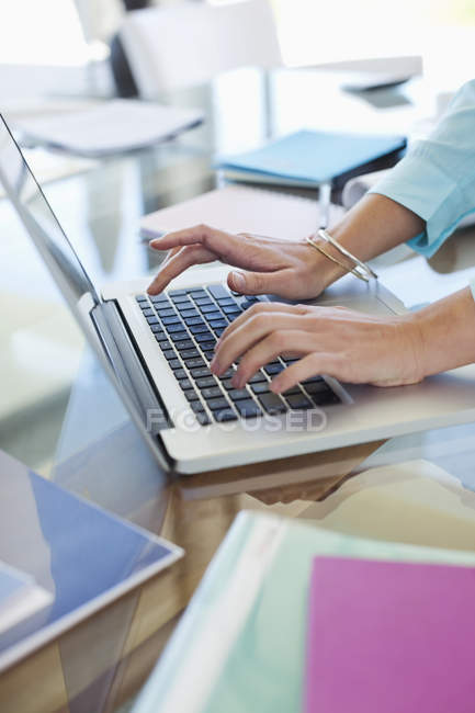 Cropped image of businesswoman using laptop at desk — Stock Photo