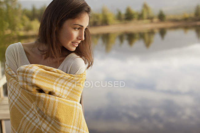 Smiling woman wrapped in blanket at lakeside — Stock Photo