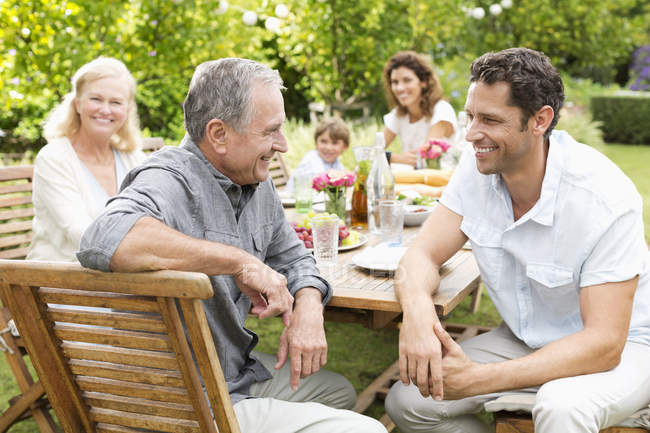 Multi generation family sitting at table outdoors — Stock Photo
