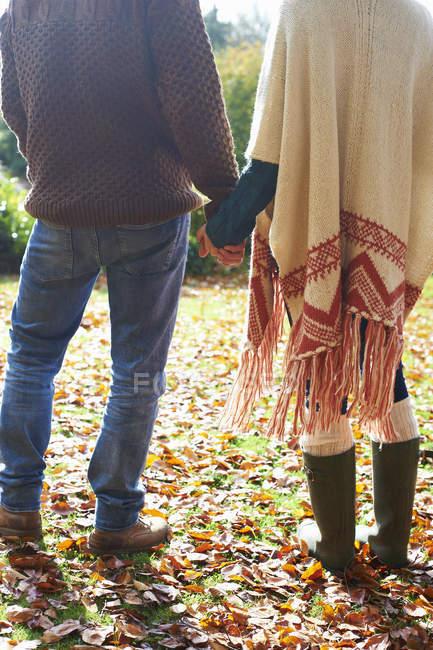 Пара, тримаючись за руки Осінні листи — стокове фото