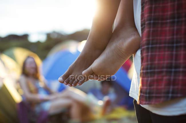 Мужчина, несущий босиком женщину на музыкальном фестивале — стоковое фото