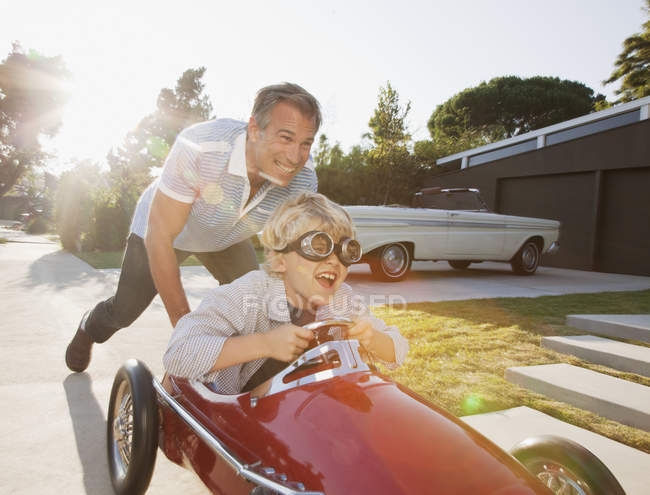Father pushing son in go cart — Stockfoto