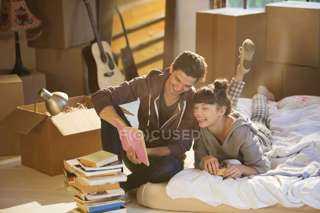 Couple unpacking books in new home — Stock Photo