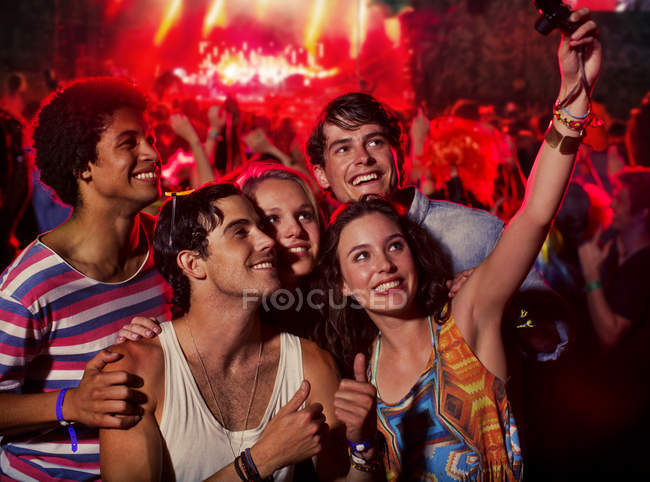 Friends taking self-portrait with camera phone at music festival — Stock Photo