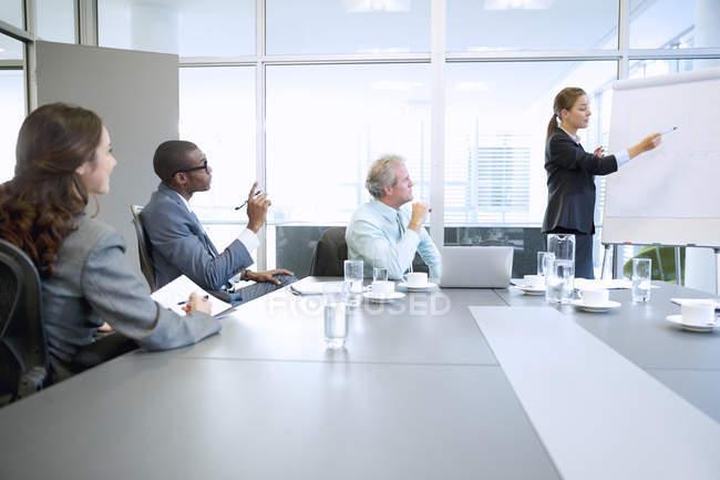 Mujer de negocios en flipchart líder de reunión en la sala de conferencias en la oficina moderna - foto de stock