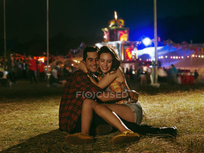 Happy couple hugging outside music festival — Stockfoto