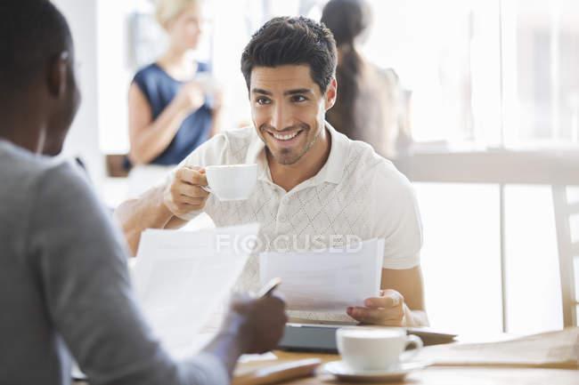 Uomo d'affari che beve caffè alla riunione nel caffè — Foto stock