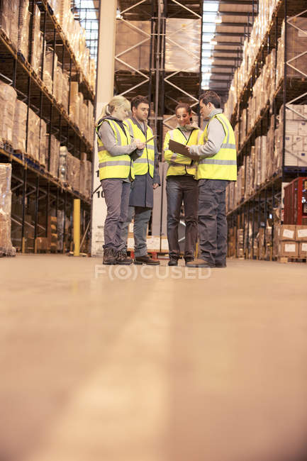 Workers talking in warehouse — Stock Photo