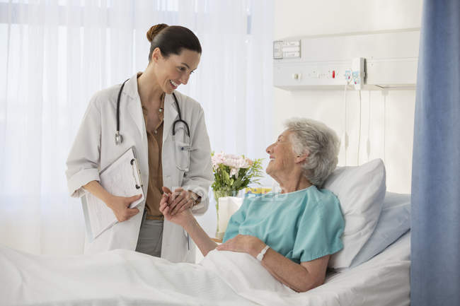 Doctor and senior patient talking in hospital room — Stock Photo