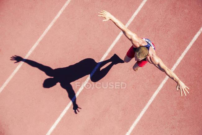 Легкоатлет прыгает по рельсам с протянутыми руками — стоковое фото
