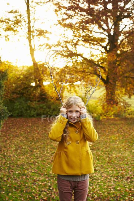 Sonriente chica rubia sosteniendo ramas como astas - foto de stock