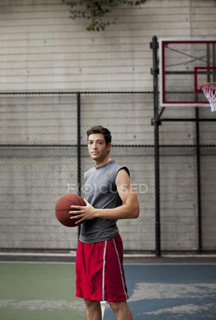 Человек, стоящий на баскетбольной площадке — стоковое фото