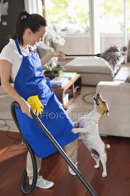 Cameriera giocare con cane in soggiorno — Foto stock