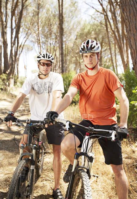 Два горных велосипедиста на грунтовой дорожке в лесу — стоковое фото