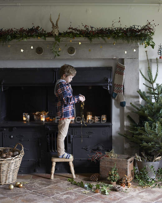 Side view of cute boy decorating Christmas fireplace — Stock Photo