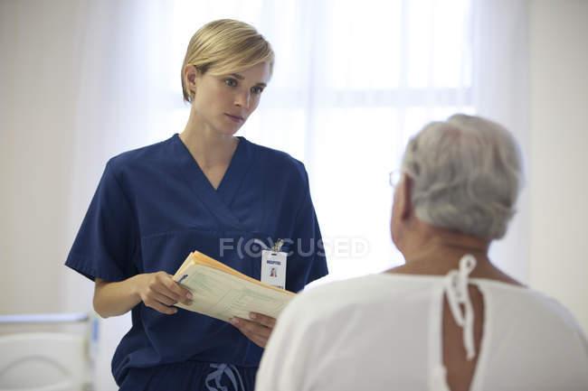 Enfermeiro e paciente idoso conversando no quarto do hospital — Fotografia de Stock