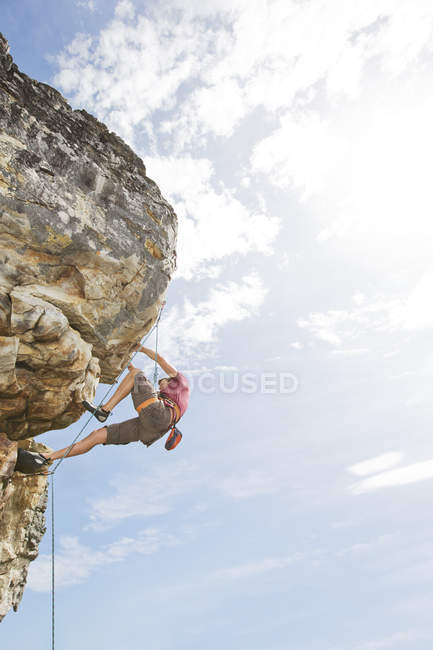 Low angle view of climber scaling steep rock face — Stock Photo