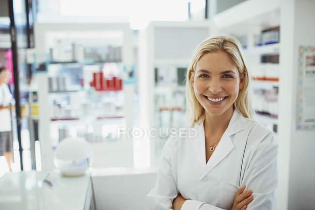 Pharmacist smiling in drugstore — Stock Photo