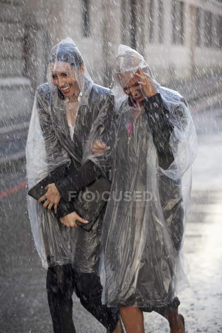 Geschäftsfrauen in Ponchos laufen durch die verregnete Straße — Stockfoto