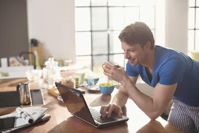 Mann benutzt Laptop mit Tasse Kaffee — Stockfoto