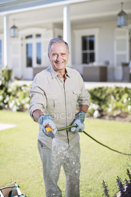 Uomo caucasico senior innaffiare le piante in giardino — Foto stock