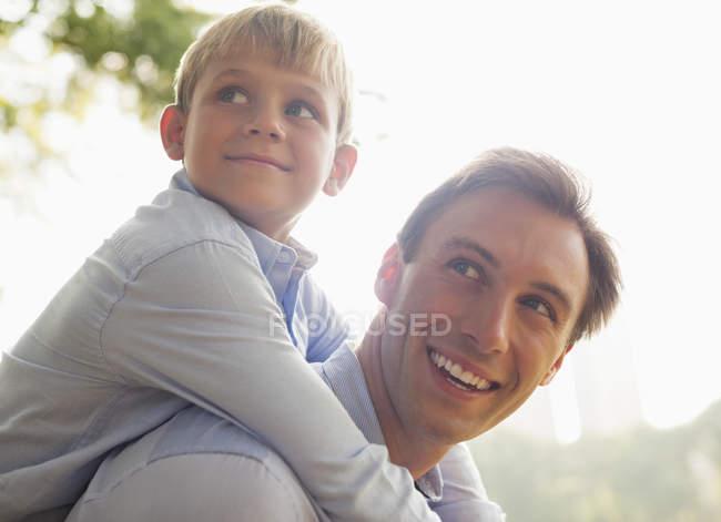 Homme portant fils piggyback à l'extérieur — Photo de stock