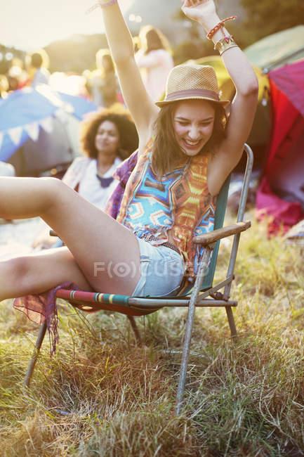 Entusiasta donna in sedia a sdraio fuori tende al festival musicale — Foto stock