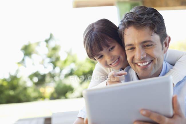 Отец и дочь вместе с помощью планшетного компьютера — стоковое фото