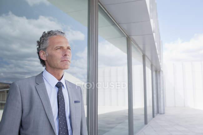 Нетерпеливый бизнесмен у здания — стоковое фото