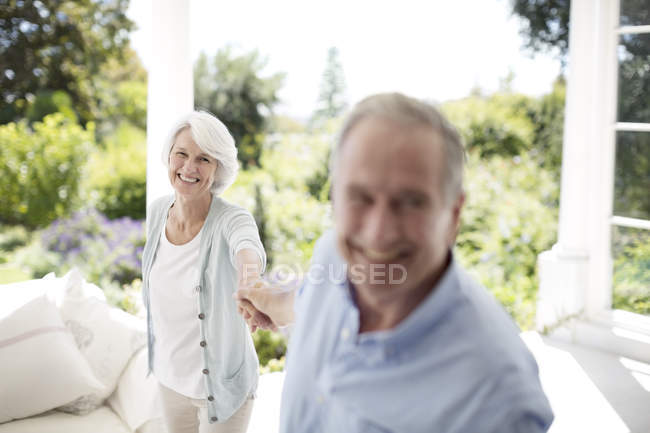 Casal sênior de mãos dadas no pátio — Fotografia de Stock