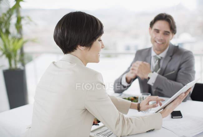 Homme d'affaires et femme d'affaires utilisant une tablette numérique à la table du restaurant — Photo de stock