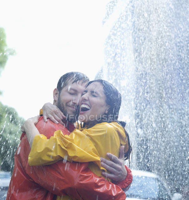 Happy caucasian couple hugging in rain — Stock Photo
