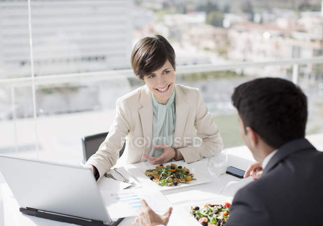 Businessman and businesswoman with laptop meeting over lunch — Stock Photo
