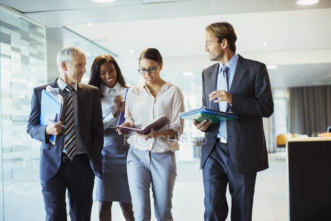 Les gens d'affaires parlent et marchent dans l'immeuble de bureaux — Photo de stock