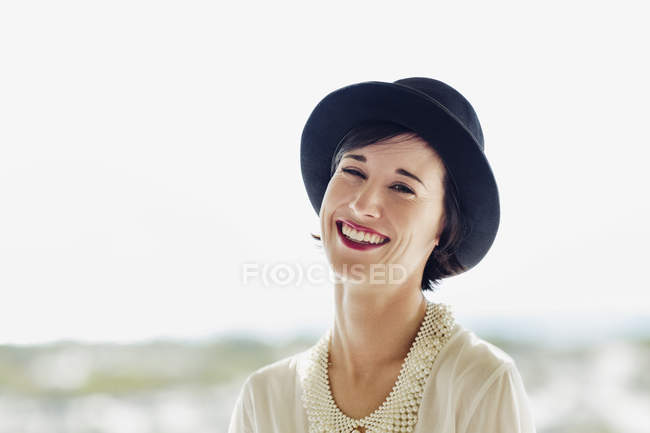 Portrait de femme souriante portant un chapeau — Photo de stock