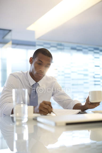 Serious businessman reading paperwork at modern office — Stock Photo