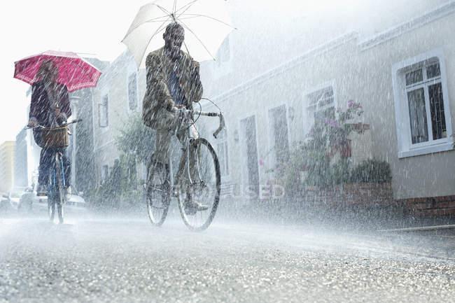 Coppia ombrelloni in sella alle biciclette sotto la pioggia — Foto stock