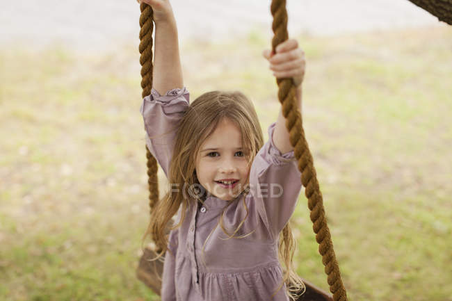 Portrait of happy smiling girl on swing — Stock Photo