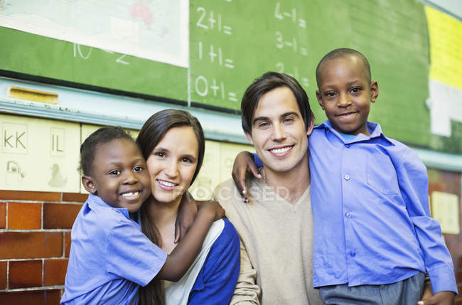 Teachers and african american students smiling in class — Stock Photo