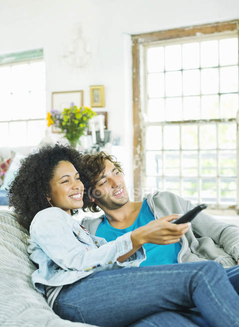Coppie che guardano la televisione in sedia beanbag — Foto stock