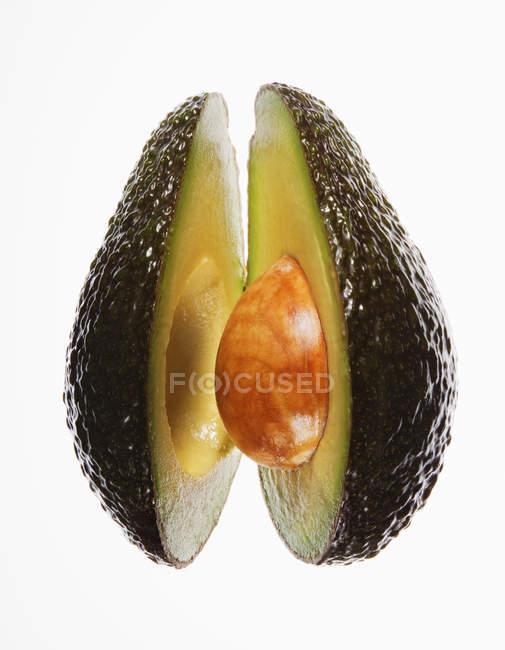Close-up da divisão de abacate sobre fundo branco — Fotografia de Stock