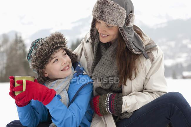 Felice madre e figlio bere cioccolata calda nel campo innevato — Foto stock
