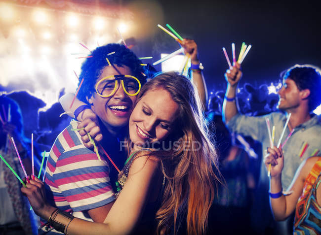 Couple with glow sticks hugging at music festival — Stock Photo