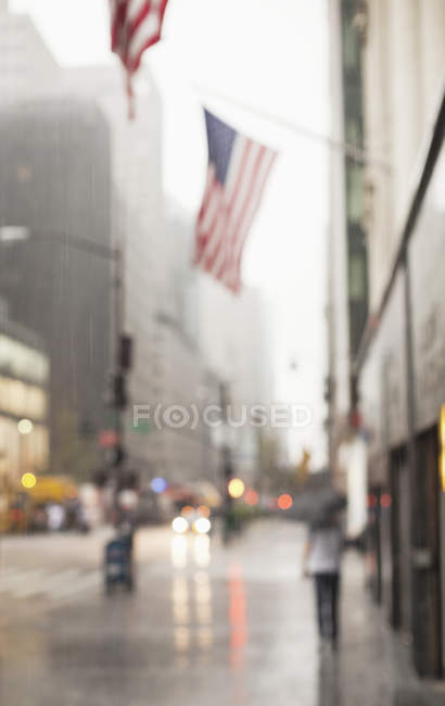 Blurred view of American flags on city street — стокове фото