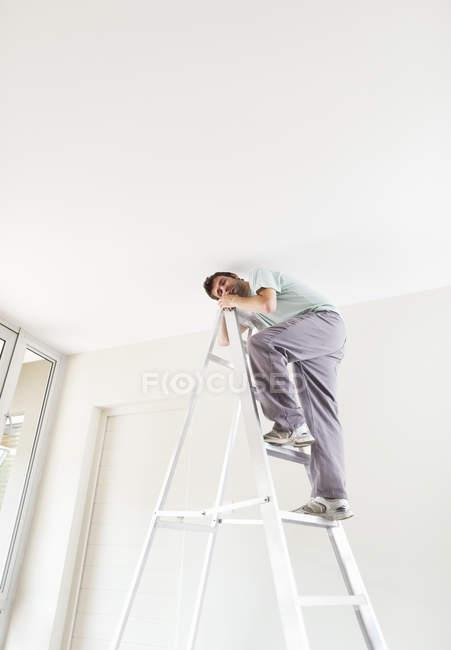 Skillful caucasian man climbing ladder indoors — Stock Photo