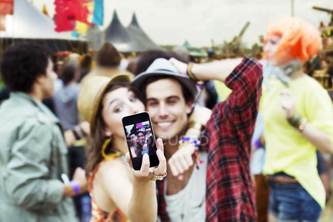 Couple prenant autoportrait avec téléphone caméra au festival de musique — Photo de stock