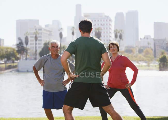 Пара пожилых людей, занимающихся с тренером в парке — стоковое фото