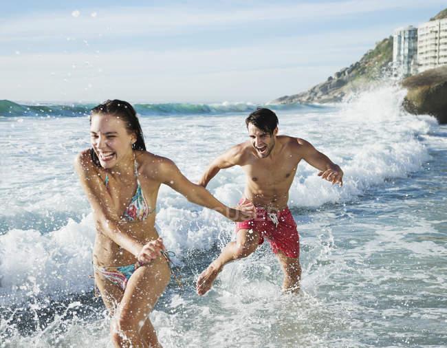 Playful couple splashing in ocean surf — Stock Photo