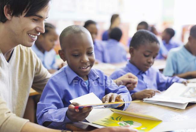 Учитель, работающий с африканским американским студентом в классе — стоковое фото