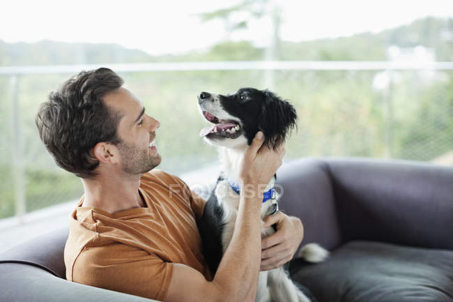Улыбающийся мужчина ласкает собаку на диване в современном доме — стоковое фото